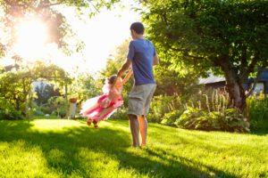 dad-swinging-daughter-on-grass